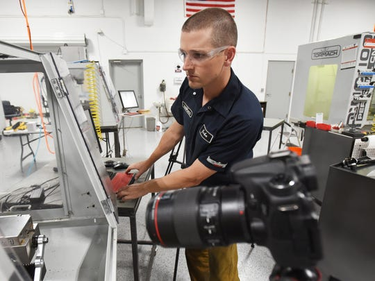 John Saunders of Saunders Machine Works sets up his CNC machine while getting ready to film at his shop in Zanesville.