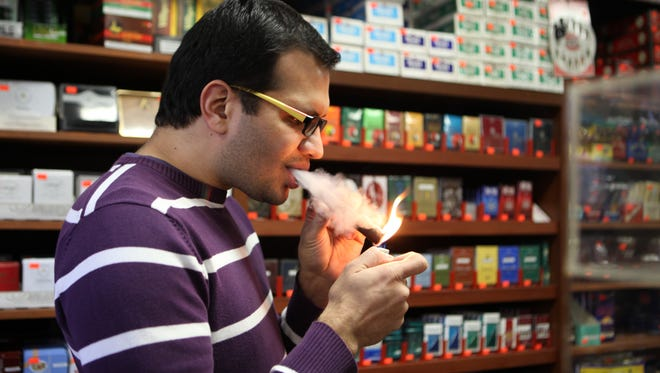 Mitul Shah, the owner of Mom's Cigar Warehouse on Central Park Avenue in Scarsdale lights up Dec. 22, 2014. The lifting of the Cuban trade embargo will have an affect on the local tobacco trade.