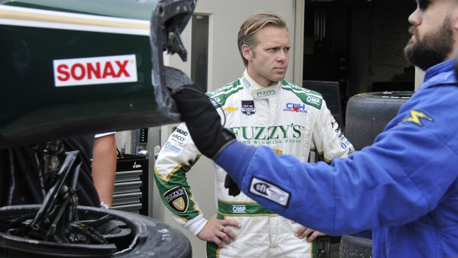 Boom truck operator Dave Reynolds holds onto Ed Carpenter's crashed car as it's unloaded in the garage area. The 2013 and 2014 pole-sitter concentrates on the task of qualifying a backup car at the Indianapolis Motor Speedway on May 17, 2015.