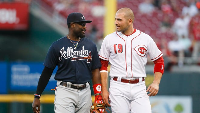 Atlanta Braves second baseman Brandon Phillips, left, meets the with Reds' Joey Votto (19) after the fourth inning Friday.