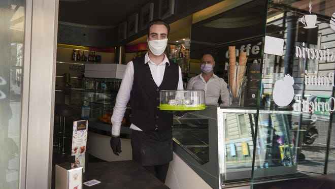 Bartender Antonio delivers coffee in Naples, Monday, April 27, 2020. Region Campania allowed cafes and pizzerias to reopen for delivery Monday, as Italy it is starting to ease its lockdown after a long precautionary closure due to the coronavirus outbreak.