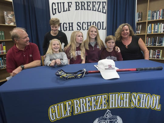Family surrounds Gulf Breeze High School's Frances Williams, center right, during signing ceremony Monday afternoon in the school's media center to continue her Lacrosse career at Lenoir-Rhyne University.