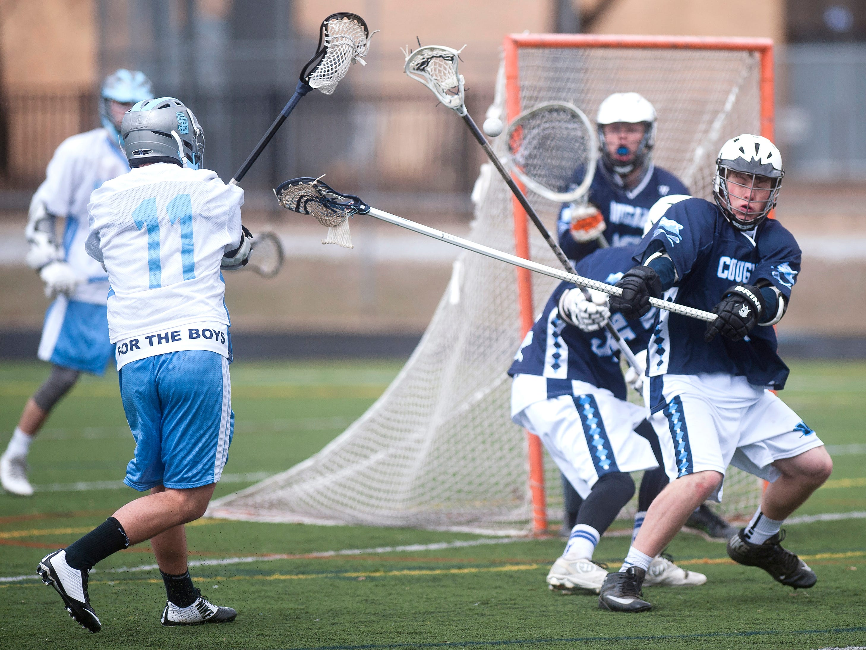 South Burlington attacker Ben Sievers (11) rifles a shot at the Mount Mansfield goal during the fourth quarter of Saturday's boys lacrosse game in South Burlington.