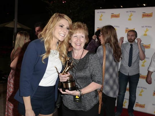 Leah Lester, right, won $5,000 for her submitted video of Buddy the cat tentatively exploring a flip-flop on her living room floor. Comedian, actress, author, and YouTube personality Grace Helbig presented her with her golden catuette.