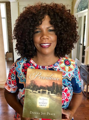 "Lynda Randle holds a copy of ""Providence – A History of Summit Grove.""  She will sing and portray evangelist Amanda Berry Smith."