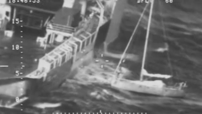 In this frame from video provided by the U.S. Coast Guard, a Frenchman with his cat tucked inside his clothing, at right, stands on his saildboat before making a leap Tuesday, Oct. 20, 2015, jumping to a waiting rescue ship, left, south of Alaska.
