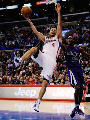 Kings forward Travis Outlaw grabs Clippers guard J.J. Redick's shoulder on a layup attempt.