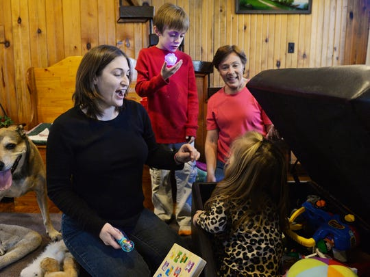 Niki Pangle, left, and her mother Connie Radziewicz greet Pangle's daughter Lily, 3, after she played hide-and-seek in the living room ottoman as Pangle's son Matthew, 8, watches in November at the Radziewicz' home in Hellam Township. Connie Radziewicz was diagnosed with stage four ovarian cancer in October 2013 and underwent about 18 months of treatment over a 2-year period.