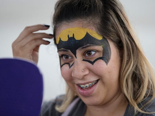 Dalila Aguirre, of Carmel, smiles in reaction to a fresh Batman face painting by Katrina Pogue at the Broad Ripple Carnival.