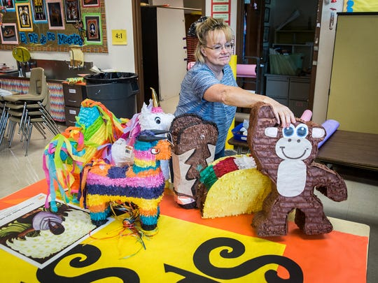 Nancy Swickard arranges piñatas in her classroom at West View Elementary School Friday morning.