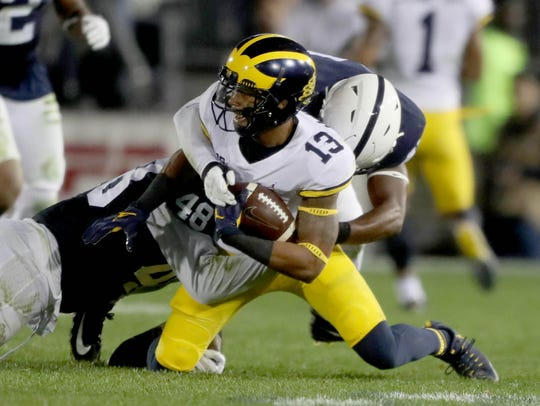 Michigan's Eddie McDoom is tackled by Penn State's