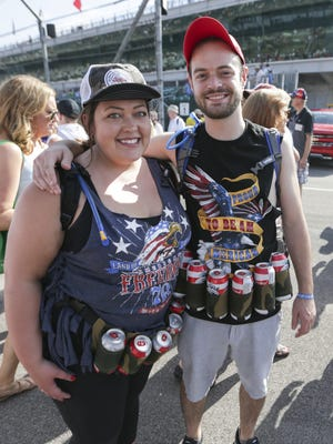 "Katie McCone, Carmel, and Wes Couch, Lafayette, show off their beer holsters at the Indianapolis Motor Speedway for the 100th running of the Indianapolis 500, Sunday, May 29, 2016. McCone, who's helping Couch carry extra booze in Camelbacks, said, ""we're just walking bars."""