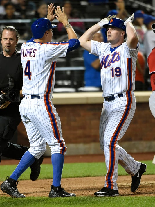 New York Mets Wilmer Flores (4) high fives with Jay Bruce (19) at home plate after Bruce hit a two-run home run that scored Flores in the sixth inning of a baseball game against the Washington Nationals, Sunday, Sept. 4, 2016, in New York. (AP Photo/Kathy Kmonicek)