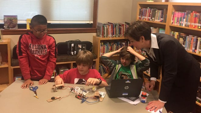 Lt. Gov. Kim Reynolds, right,chats with three students building a robotic arm at Greenwood Elementary School in Des Moines on Monday, May 1, 2017. From left, Tegan Van-Ngoy, 11; Ivan Kelley, 11; and Jack Keenan, 11, all fifth graders.