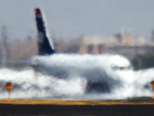 A jet taxis and appears to melt into the asphalt as