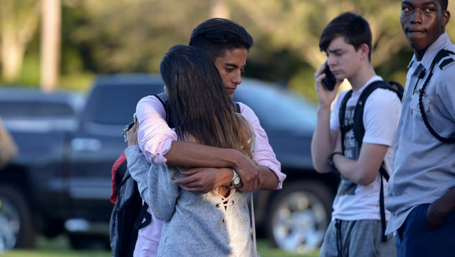 "Jorge Zapata, 16, a student at Marjory Stoneman Douglas High School in Parkland, embraces his mother, Lavinia Zapata, both of Parkland, after a mass shooting Wednesday, Feb. 14, 2018, earlier in the day at the school. ""I was just really incredibly, indescribably happy to see him, because you never know,"" Lavinia Zapata said."