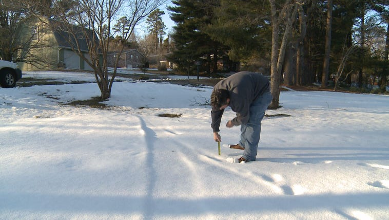 Wade Johnson measures the snow outside his home in