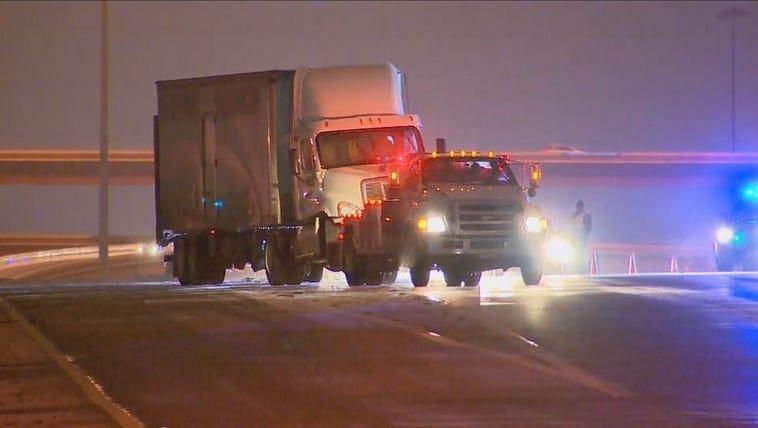 A tow truck pulls an 18-wheeler.