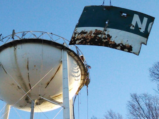 "Rusted one-ton steel sections bearing the ""North Liberty"" name are lowered by crane Thursday morning from the 140-foot deactivated water tower."