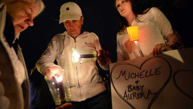Elaine Derstine, left, Michelle Smith, and Cheryl Swanson, light their candles for the vigil. A candlelight vigil was held in Loomiller Park in Longmont, Colo., for Michelle Wilkins and her baby Sunday, March 22, 2015.