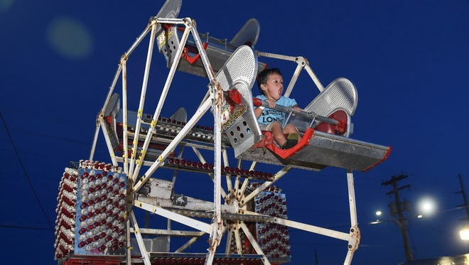 Hunter Bernardo, 4, displays excitement while riding the kiddie Ferris wheel at the Liberation Carnival in Tiyan on July 4.
