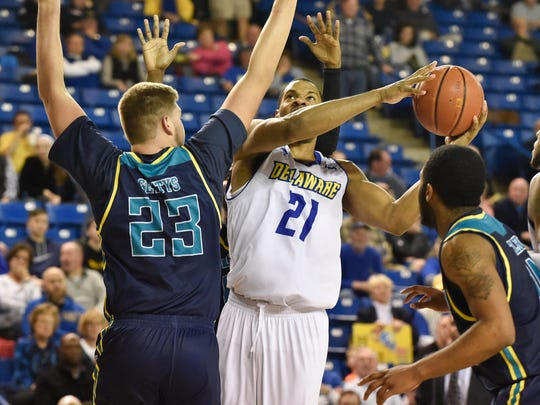 Delaware's Marvin King-Davis (21) jumps up for a shot as UNCW's C.J. Gettys (23) defends.