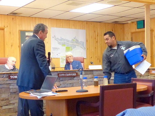 Isaac Garcia, wastewater treatment plan manager, illustrates the final product from the plant by showing three jars, the dark being what arrives at the plant. At left is Del Archuleta.