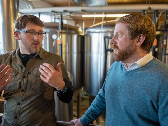 Brewmaster Tristin Bradford and Jeremiah Johnson, owner of Jeremiah Johnson Brewing Co., talk during production of the Golden Bobcat Pale Ale at their Great Falls facility.