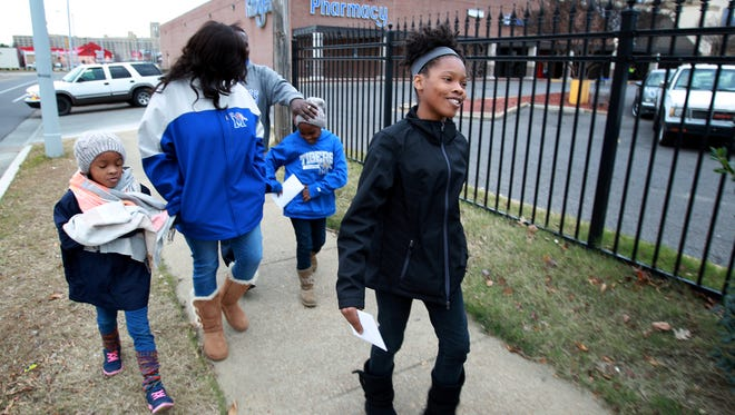 Lauryn Brownlee, 11, right, leads her family Victoria, 7, from left, Kewanee, Louis and Kaitlyn, 9, down Cleveland as she randomly gives out $20 gift certificates to strangers on Dec. 20. The children are charged $5 per month rent through the year and given the money back at the end of the year. For the second year all three chose to give random blessings to strangers.