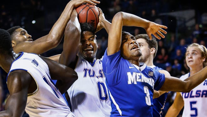 University of Memphis forward Dedric Lawson (left) battles Tulsa University defender Junior Etou (middle) for a rebound as Jeremiah Martin (right) is pushed out of the play during first-half action at the Donald W. Reynolds Center in Tulsa, Oklahoma.