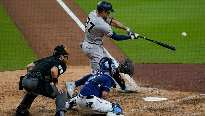 New York Yankees designated hitter Giancarlo Stanton (27) connects for a grand slam home run against the Tampa Bay Rays during the ninth inning in Game one of a baseball American League Division Series Monday, Oct. 5, 2020, in San Diego.