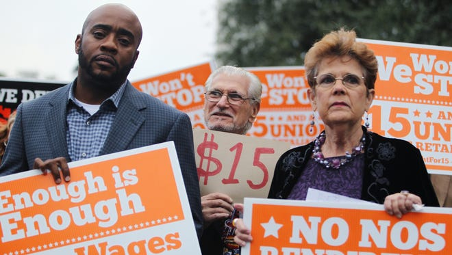 State Rep. Alan Williams, Wakulla County Commissioner Howard Kessler and organizer Barbara DeVane hold signs at a Tuesday rally urging lawmakers to raise the minimum wage to $15 an hour.