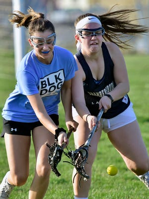 Chambersburg's Hannah Raines, left, and Mackenzie Miller battle for the ball during Trojan lacrosse practice on Friday, April 13, 2018.