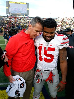 Head coach Urban Meyer of the Ohio State Buckeyes celebrates with Ezekiel Elliott #15 after a 42-13 Ohio State win over the Michigan Wolverines at Michigan Stadium on November 28, 2015 in Ann Arbor, Michigan.