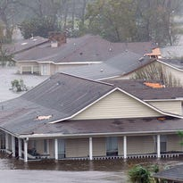 Houses with roof damage sit in floodwater from the Biloxi River by Interstate 10 in Biloxi after Hurricane Katrina passed through Mississippi on Aug. 29, 2005.