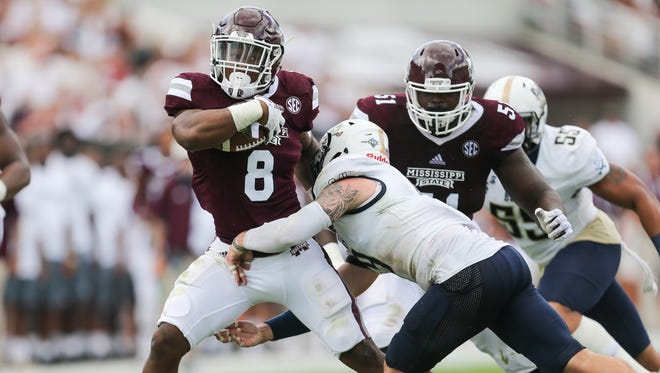 Mississippi State's Kylin Hill (8) tries to break the tackle by Charleston Southern's Demetri Royer (9).