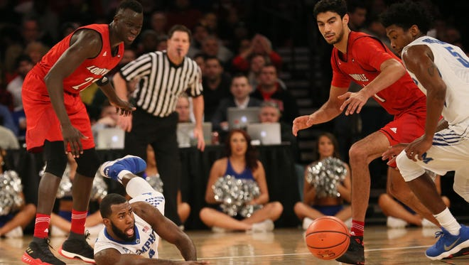 Memphis Tigers forward Raynere Thornton (4) dives for a loose ball against Louisville Cardinals forward Deng Adel (22) and forward Anas Mahmoud (14) in the first half at Madison Square Garden in New York on Saturday, Dec. 12, 2017.