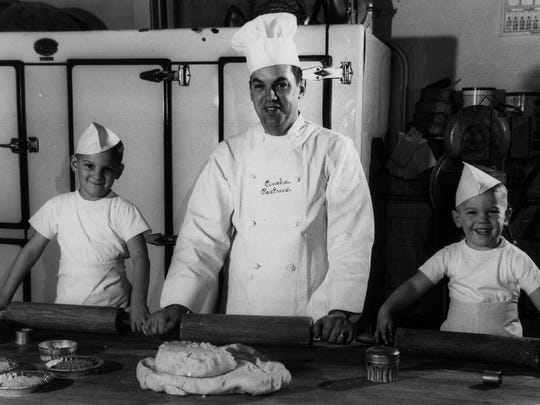 Chris Pinahs (left) rolls out dough with his father George Pinahs and younger brother Carl at the family bakery in about 1956.