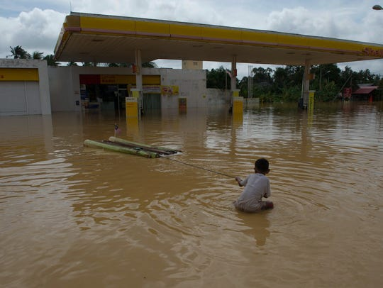 A boy plays in floodwaters near a gas station in Pengkalan