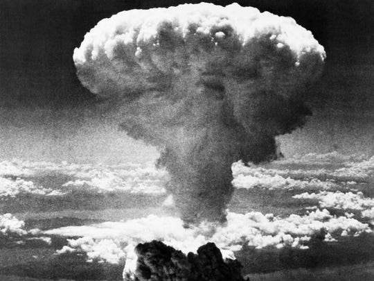 A mushroom cloud rises moments after the atomic bomb