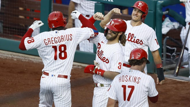 The Phillies' Didi Gregorius (18) celebrates with Bryce Harper (3), J.T. Realmuto (10) and Rhys Hoskins (17) after hitting a grand slam off Atlanta Braves pitcher Robbie Erlin during the sceond inning Monday night in Philadelphia.