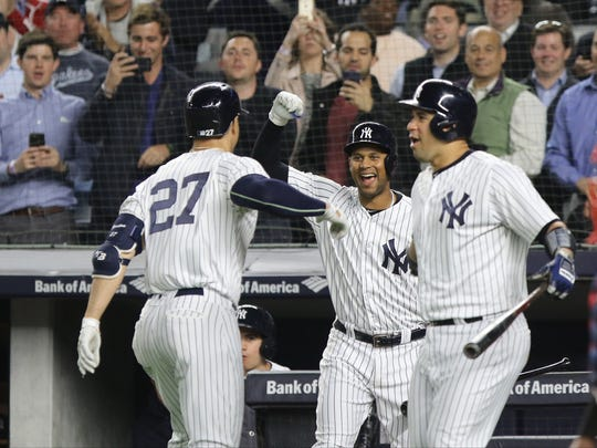 In the fourth inning Giancarlo Stanton is greeted at home by Aaron Hicks and Gary Sanchez after Stanton hit his second solo home run of the game.