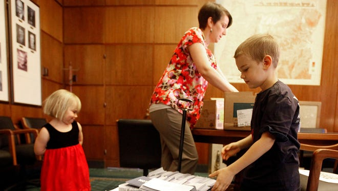 Finn Murray, 6, of Portland, helps unload a wagon of almost 16, 000 postcards that were brought by the Oregon chapter of Moms Demand Action for Gun Sense in America to Gov. John Kitzhaber's Capitol office Thursday June 19, 2014. The goal was to raise awareness and support for changing Oregon's gun laws.