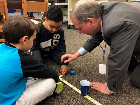 Sen. John Eichelberger Jr. (right) tests a catapult with second-graders Nathan Weis (left) and Jeyani Ghee (middle) during a STEM lesson the morning of Monday, March 5 at Hamilton Heights Elementary School in Chambersburg.