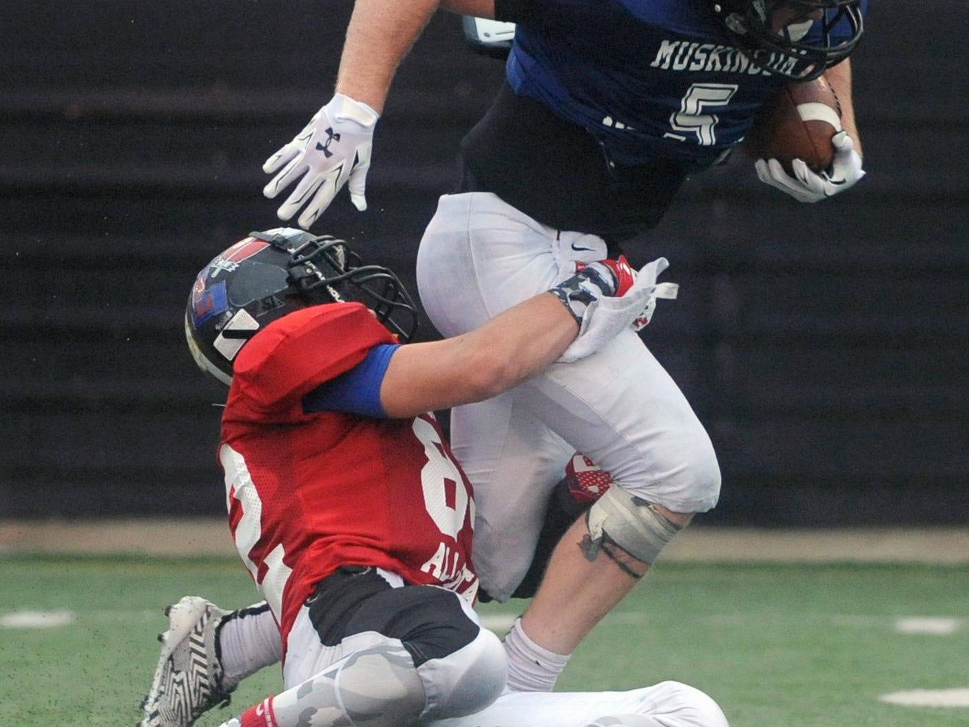 Licking County's Cameron Smith wraps up Muskingum Valley's Logan Bash in the second quarter of the Licking-Muskinumg All-Star Game this past Friday at Tri-Valley. Smith was one of four Watkins Memorial graduates playing in the game.