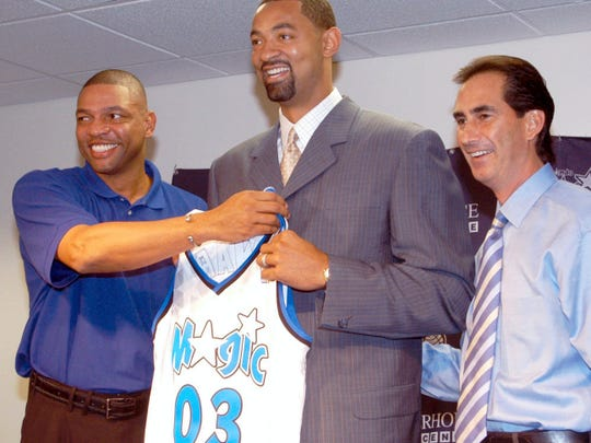 Forward Juwan Howard, center, with then-Orlando Magic head coach Doc Rivers, left, and then-general manager John Gabriel, pose with a Magic jersey in Maitland, Florida in July 2003, after Howard signed a contract with the team.