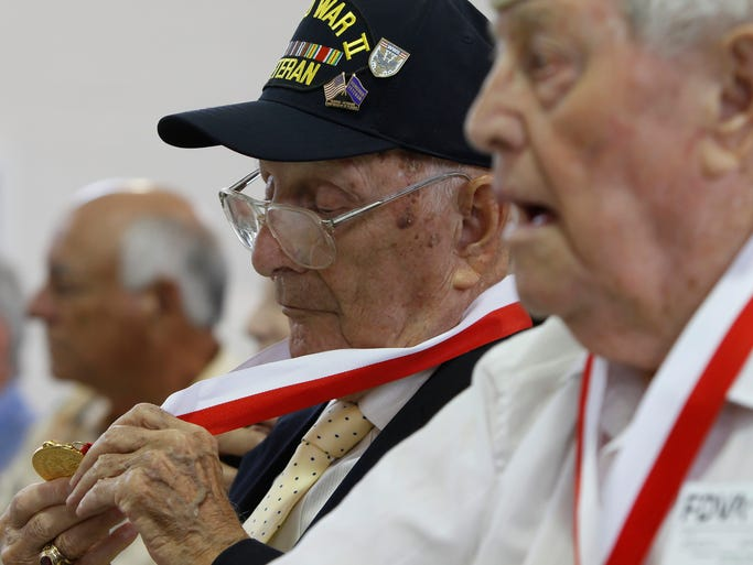WW II Army veteran Mario Grossi, center, examines his medal during the Governor's Veterans Service Award Ceremony, held at the Battery B, 3rd Battalion 265th Air Defense Artillery Regiment in Fort Myers, FL Monday, June 30. Grossi fought in the Battle of the Bulge.