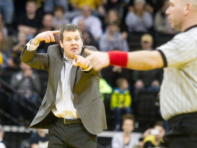 Head coach Tom Brands signals to the official while Iowa's Brody Grothus wrestles Michigan's Eric Grajales at 149-pounds during the Hawkeyes final home meet against the Wolverines in Iowa CIty on Sunday, February 9, 2014.