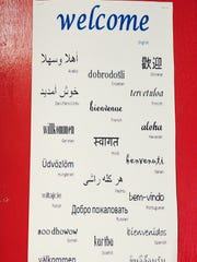 """A sign that says """"welcome"""" in many languages hangs"""