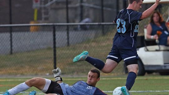 From left, Mamaroneck goal keeper Dante Rhodes seems to block a shot from John Jay's Kevin Turi (23) but was called for a foul resulting in a penalty kick that was good for a Joh Jay goal during boys soccer action at Mamaroneck High School Sept. 3, 2015. Mamaroneck won the game 2-1 in sudden death overtime with Alma scoring both Mamaroneck goals.